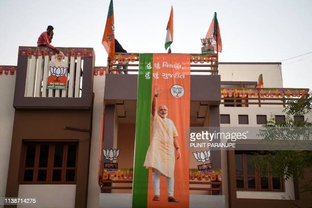 Indian residents put up Bharatiya Janata Party flags and posters of Prime Minister Narendra Modi on their house in Ahmedabad on April 22 the day...