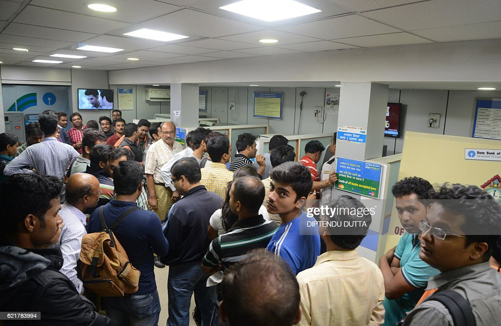 Indian residents queue to deposit money in a Cash Deposit Kiosk in Siliguri on November 8 2016 Indian Prime Minister Narendra Modi announced late...