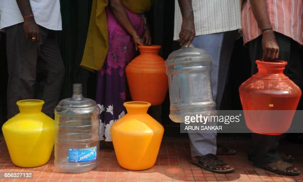 Indian residents queue with plastic containers for purified drinking water from a government distribution centre in Chennai on March 22 on World...