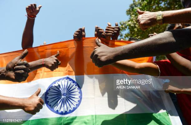 Indian residents raise their thumbs in front of the national flag as they participate in a demonstration to support Indian armed forces in Chennai on...