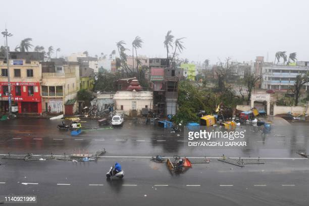 Indian residents ride along a road next to damaged trees oafter Cyclone Fani landfall in Puri in the eastern Indian state of Odisha on May 3 2019 Two...
