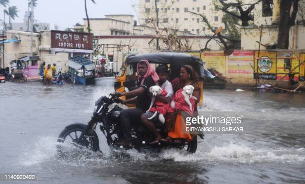 Indian residents ride on a bike along a flooded road after Cyclone Fani landfall in Puri in the eastern Indian state of Odisha on May 3 2019 Two...