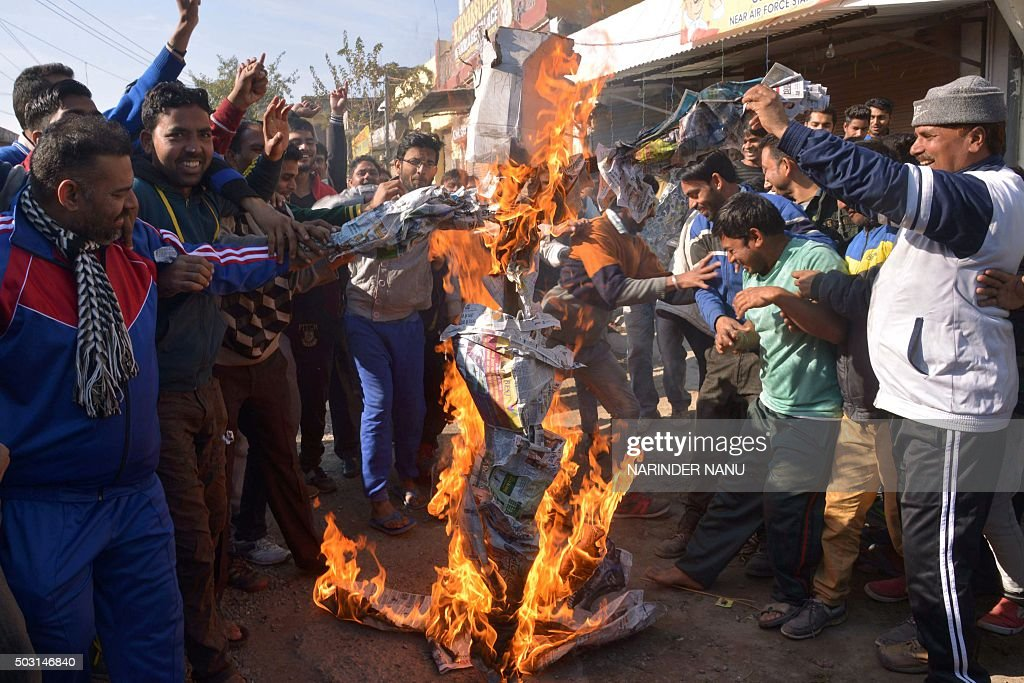 Indian residents set fire to an `effigy` on a road leading to an airforce base in Pathankot on January 2 during an ongoing attack on the base in the..