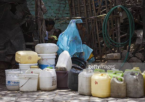 Indian residents sit near empty water containers as they wait for a government water supply truck in New Delhi on May 22 2013 With summer...