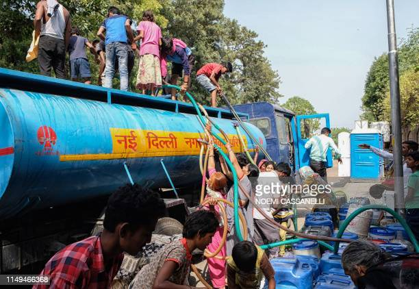 Indian residents use hoses to collect drinking water from a tanker truck during a hot summer day in the lowincome neighbourhood of Sanjay camp in New...