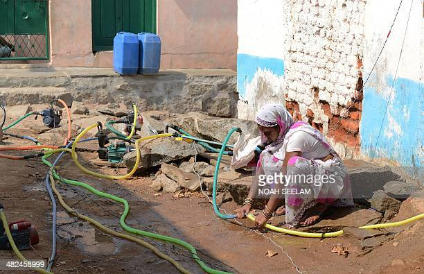 Indian residents use motors to pump potable drinking water from a government water supply pipe line on the outskirts of Hyderabad on April 3...
