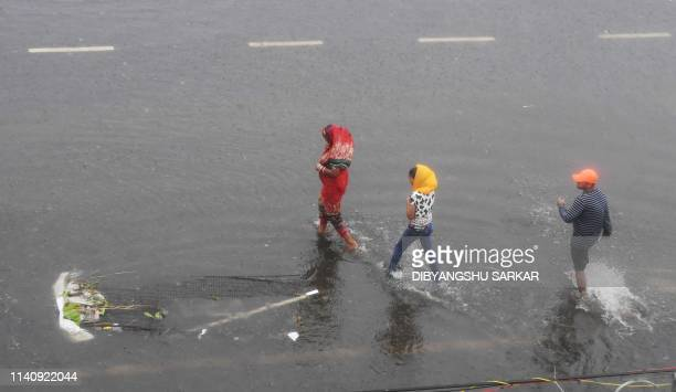 Indian residents wade along a partially flooded street after Cyclone Fani landfall in Puri in the eastern Indian state of Odisha on May 3 2019 Two...