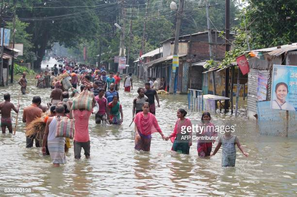 TOPSHOT Indian residents wade through flood waters in Balurghat in West Bengal on August 17 2017 At least 221 people have died and more than 15...