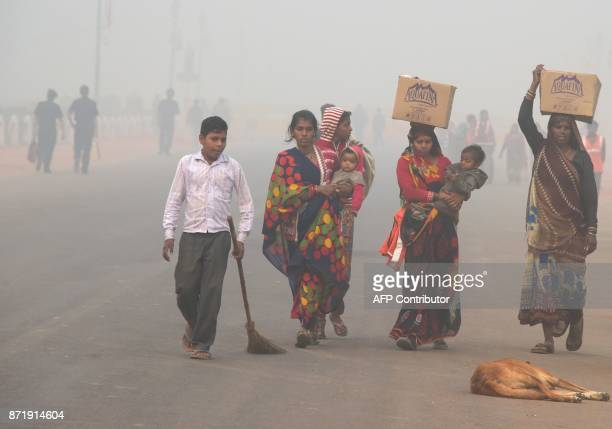 TOPSHOT Indian residents walk along a road amid heavy smog in New Delhi on November 9 2017 Rickshaw driver Sanjay can only afford a handkerchief to...