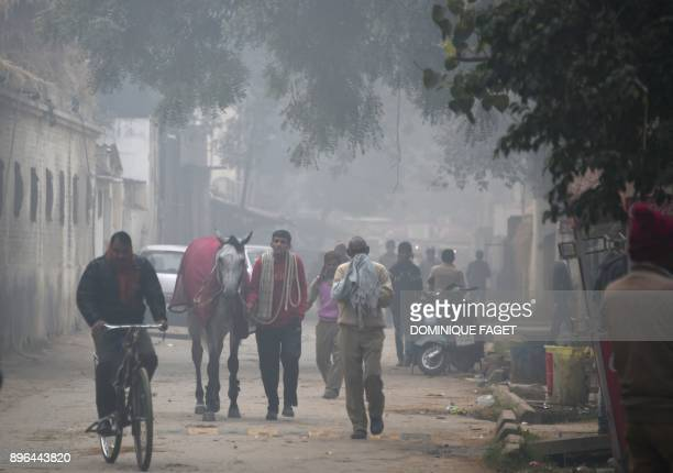 Indian residents walk amid heavy smog near the Delhi Race Club in New Delhi on December 21 2017 / AFP PHOTO / Dominique Faget