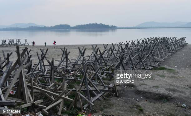 Indian residents walk near a wooden structure used to reduce erosion along the river Brahmaputra in Guwahati on April 12 2018 Brahmaputra is one of...