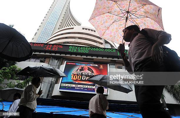 Indian residents walk past the Bombay Stock Exchange during intraday trading at a brokerage house in Mumbai on September 1 2014 The benchmark 30...