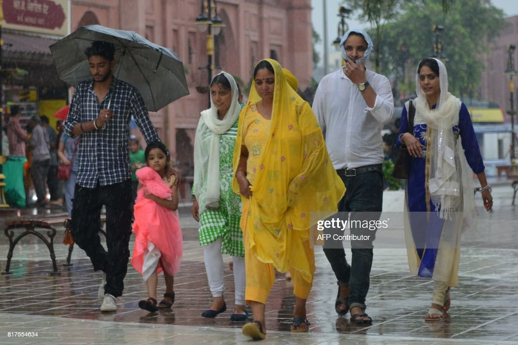 Indian residents walk through heavy rain in Amritsar on July 182017 / AFP PHOTO / NARINDER NANU