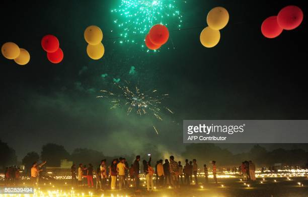 Indian residents watch fireworks at the Madan Mohan Malviya stadium on the eve of the Hindu festival of Diwali in Allahabad on October 18 2017 Diwali...