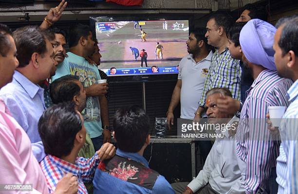 Indian residents watch the live broadcast of the Cricket World Cup match between Indian and Australia at a tea stall in Amritsar on March 26 2015 The...
