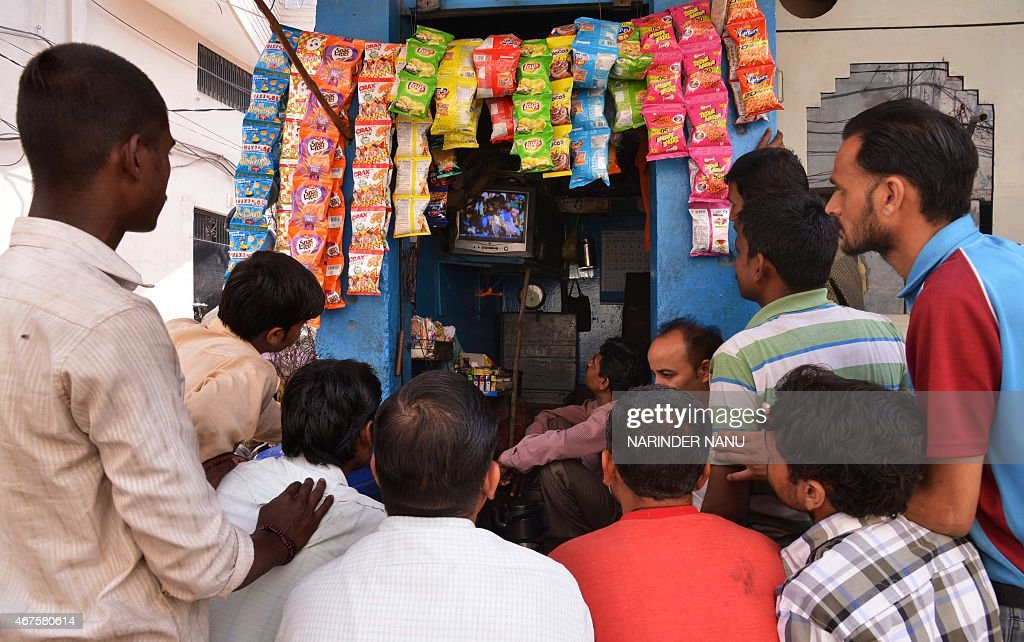 Indian residents watch the live broadcast of the Cricket World Cup match between Indian and Australia at a tea stall in Amritsar on March 26, 2015