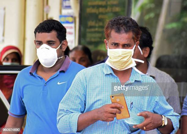 Indian residents wear face mask outside the Medical College hospital in Kozhikode on May 21 2018 A deadly virus carried mainly by fruit bats has...