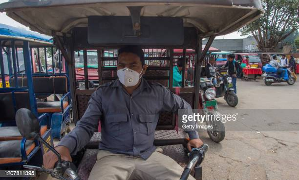 Indian rickshaw driver wearing a protective mask waits for passengers to carry them outside the historic Jama Masjid amid the government imposing...