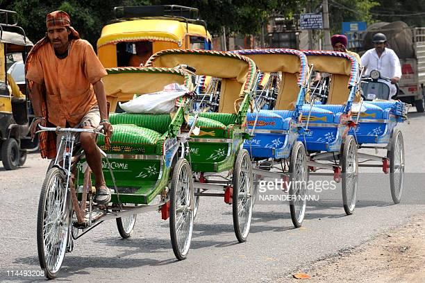 Indian rickshaw puller Jarnail Singh transports new velo rickshaws at the roadside in Amritsar on May 22 2011 Heavy rains on May 21 in several areas...