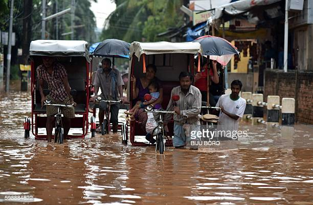Indian rickshaw pullers transport customers through floodwaters in the Anilnagar area of Guwahati on September 3, 2016.