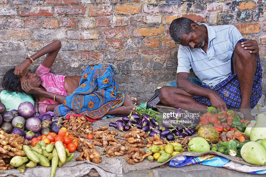 Indian roadside vegetable sellers rest while waiting for customers in Amritsar on August 27 2014 India`s wholesale price inflation hit a fivemonth...