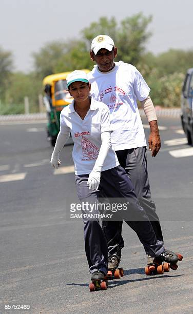 Indian rollerskater Sheetal Pandya skates along with her father Jagdish Pandya along the Kalol highway some 30 kms from Ahmedabad on April 1 2009...