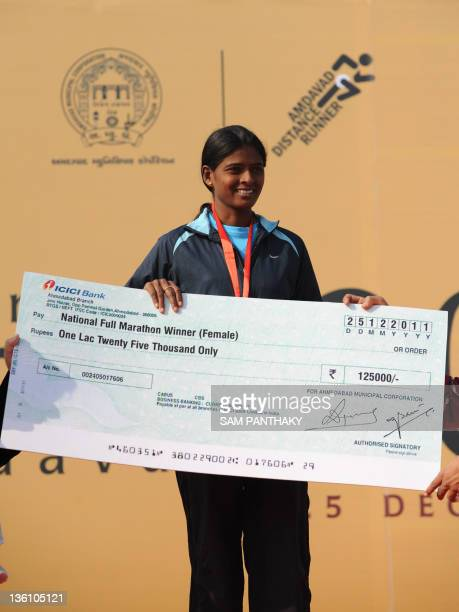 Indian runner Preeti Rao poses with her winning cheque and trophy for winning the women's National Full Level category of the Sabarmati Marathon 2011...