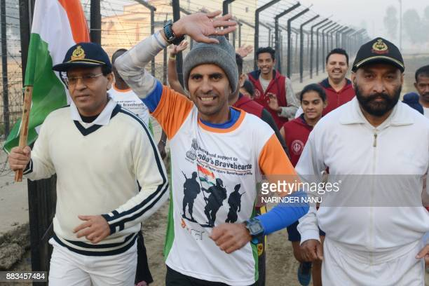 Indian runner Samir Singh and Indian Border Security Forces Deputy Inspector General JS Oberoi and BSF Commandant Sudeep take part in the start of...