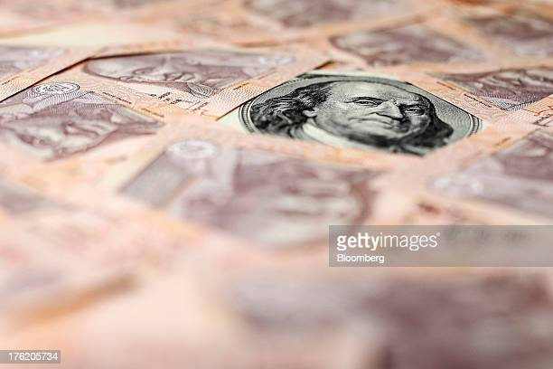 Indian rupee and US dollar banknotes are arranged for a photograph in Mumbai India on Saturday Aug 10 2013 India plans to sell 220 billion rupees of...