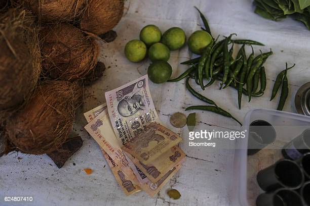 Indian rupee banknotes sit at a stall outside a Hindu temple in Mumbai India on Saturday Nov 19 2016 India's top court refused to stay petitions...
