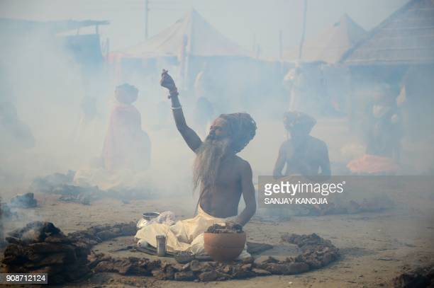 TOPSHOT Indian Sadhus or holy men perform a ritual by burning dried cow dung cakes in earthen pots at Sangam confluence of rivers Ganges Yamuna and...