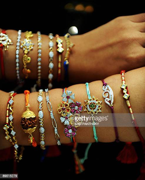 Indian sales girls display Jewel Rakhis ahead of Raksha Bandhan at the Forever Jewellery Showroom in Ahmedabad on July 30 2009 The rakhis made of...