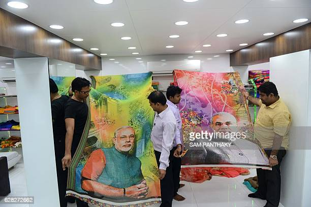 Indian salesmen show samples of sarees with photos of Indian Prime Minister Narendra Modi at a showroom in Surat some 270 kms from Ahmedabad on...