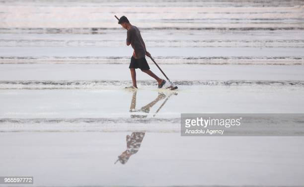 Indian salt lake workers rack salt at a salt pan in Mumbai India on May 07 2018