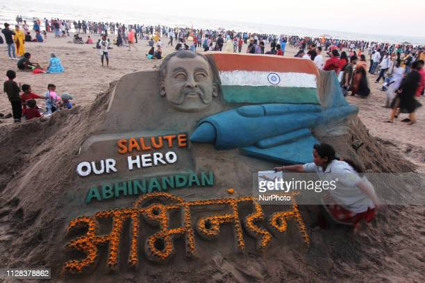 Indian sand artist Laxmi Gaud gives the finishing touch to a sand sculpture paying tribute to the return of Indian Air Force pilot Abhinandan...
