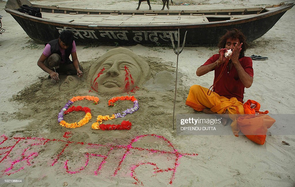 Indian sand artist Rajkumar Chittera (L) works on a sand sculpture as he pays homage to those killed in the Bailla boat accident at Sangam in Allahabad on June 16, 2010. At least 62 people drowned when their boat capsized during a prayer ceremony on the river Ganges on June 14 at Bailla district, Uttar Pradesh in Northern India. AFP PHOTO/Diptendu DUTTA