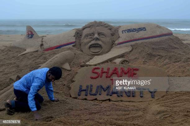 Indian sand artist Sudarsan Pattnaik is pictured with his sand sculpture honouring victims of Malaysia Airlines flight MH17 which appears to have...
