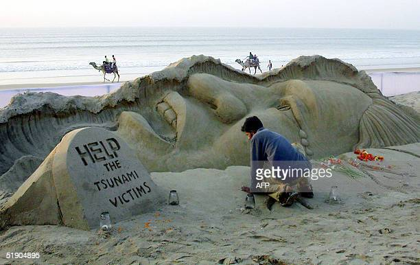 Indian sand artist Sudarshan Patnaik completes a sculpture in memory of the victims of the tsunami disaster in Puri some 100 Kms south of the capital...
