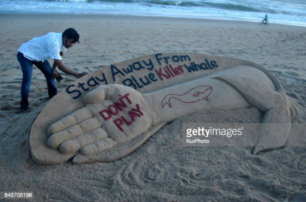 Indian sand artist Sudarshan Patnaik is creating a sand sculpture about the Blue Whale game for public awareness at the Bay of Bengal Seas eastern...