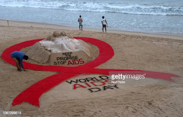 Indian sand artist Sudarshan Pattnaik creating a red ribbon at the Bay of Bengal Sea's eastern coast Konark beach, 65 km away from the eastern Indian...