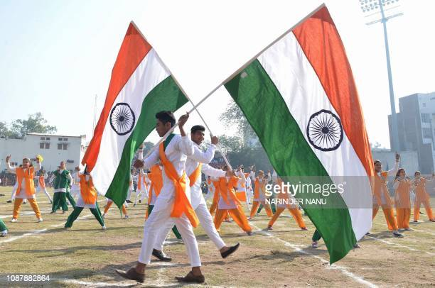 Indian school boys hold national flags as they participate in a full dress rehearsal for the upcoming 70th Republic Day parade in Amritsar on January...