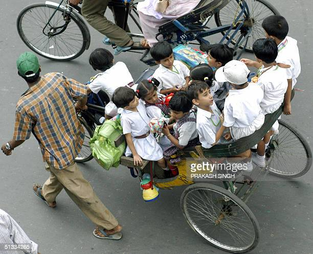 Indian school children are taken home by a rickshaw puller after their day at school in New Delhi 22 September 2004 Despite India's economic boom its...
