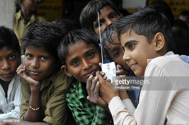 Indian school children crowd around a radio as they listen to a broadcast by Indian Prime Minister Narendra Modi delivering his Teachers' Day speech...