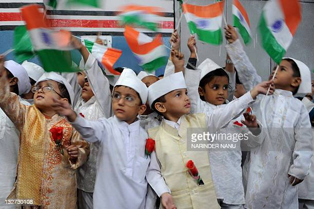 Indian school children dressed up as India's first prime minister Jawaharlal Nehru wave the Indian national flag during celebrations for Children's...