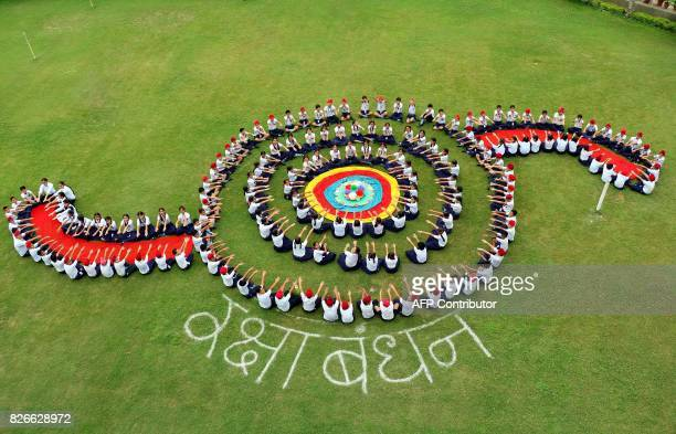 Indian school children form the shape of a 'Rakhi' at a their school ahead of the upcoming festival of Raksha Bandhan in Patiala on August 5 2017 /...