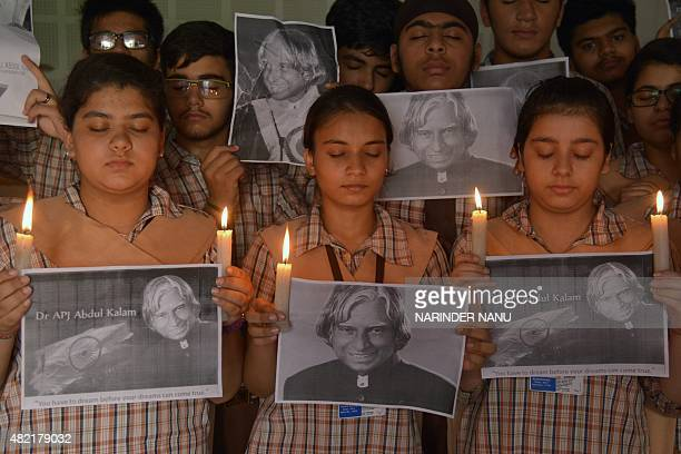 Indian school children hold candles as they pay homage to India's former president APJ Abdul Kalam at a school in Amritsar on July 28 2015 India's...