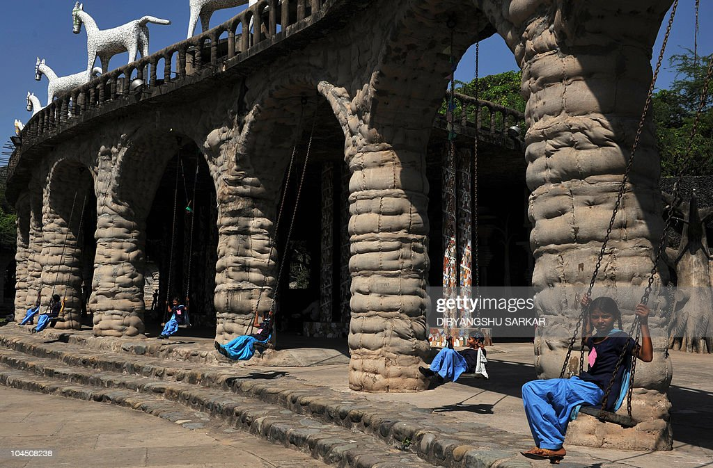 Indian school children share a swing inside the Rock garden in Chandigarh on September 28 2010 Rock Garden is a sculpture garden founded by Nek Chand.