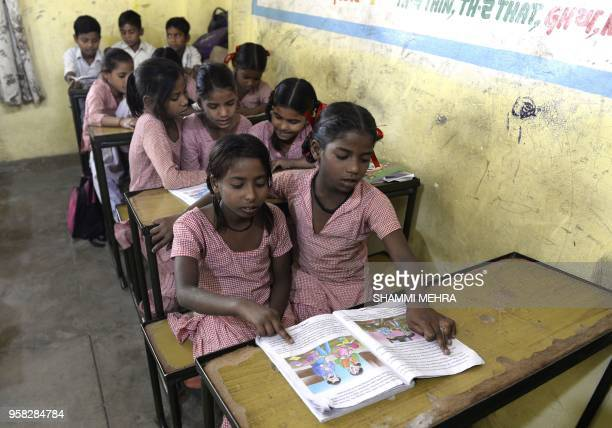 Indian school children sit in a classroom before taking vaccination for measles and rubella at a government school in Jalandhar on May 14 2018 Punjab...