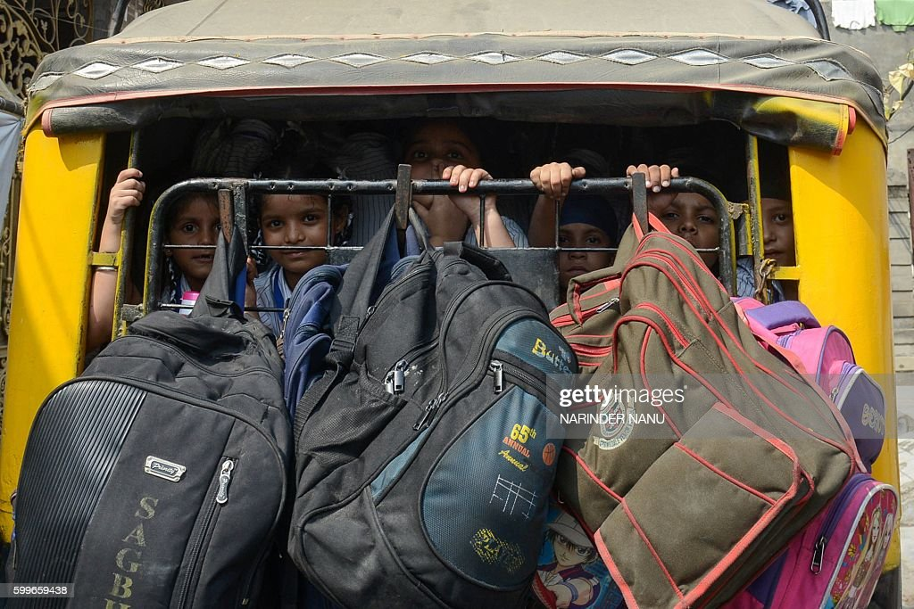 Indian school children sit in an auto rickshaw behind their bags as they return from a school in Amritsar on September 6 2016 / AFP / NARINDER NANU