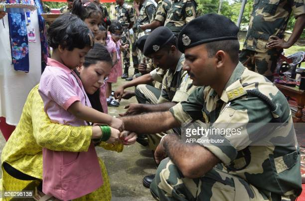 Indian school children tie 'rakhi' onto the wrists of Indian Border Security Force personnel ahead of the Hindu festival Raksha Bandhan at Datrapara...